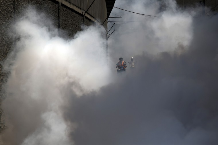 People on a motorcycle ride through a cloud as a truck from the Sucre municipality is used to carry out fumigation to help control the spread of Chikungunya and dengue fever, viruses which are carried by mosquitoes, in the Petare slum district of Caracas September 22, 2014. Medical shortages have complicated Venezuela's efforts to treat outbreaks of mosquito-borne fevers, creating long lines at pharmacies to buy analgesics and leaving the ill without ways to control the swelling joints and aching bones that the disease causes. Venezuela has South America's highest incidence of chikungunya, a virus of African origin whose name comes from a Tanzanian term for being doubled-over in pain. It also has the fourth-highest incidence of dengue on the continent this year. (Carlos Garcia Rawlins/Reuters)