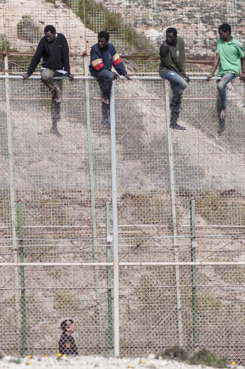 African migrants sit on top of a border fence covered in razor wire between Morocco and Spain's north African enclave of Melilla during their latest attempt to cross into Spanish territory. Spain has more than doubled the strength of security forces at Melilla, after about 500 people stormed its fences in the biggest border rush for years earlier this month. Immigrants from all over Africa regularly dare the razor-wire fences of Spanish enclaves Ceuta and Melilla, which are surrounded by Moroccan territory and sea. (REUTERS/Jesus Blasco de Avellaneda)