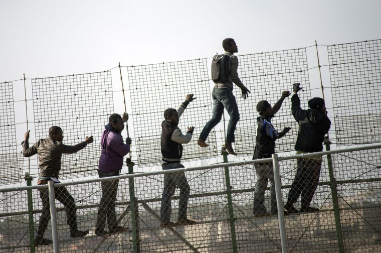 African migrants climb a border fence covered in razor wire during their latest attempt to cross into Spanish territory between Morocco and Spain's north African enclave of Melilla on May 1, 2014. (REUTERS/Jesus Blasco de Avellaneda)