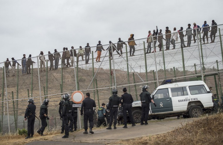 African migrants climb a border fence, as Spanish Civil Guard officers stand under them, during a latest attempt to cross into Spanish territory, between Morocco and Spain's north African enclave of Melilla on May 17, 2014. (REUTERS/Jesus Blasco de Avellaneda)
