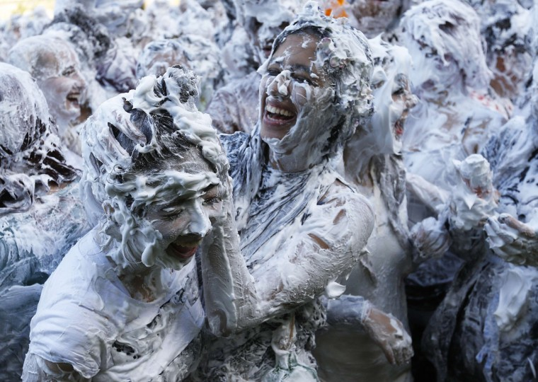 Students from St Andrews University are covered in foam as they take part in the traditional 'Raisin Weekend' in the Lower College Lawn, at St Andrews in Scotland October 20, 2014. The weekend, which begins on Sunday, involves rituals for new students, culminating in a foam fight on Monday morning. (Russell Cheyne/Reuters)