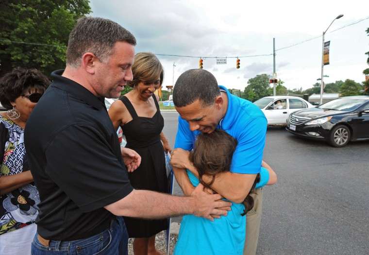 6/25/14: Democratic gubernatorial candidate Lt. Gov. Anthony Brown, center, is greeted with a hug from Lily Ulman, 8, the daughter of his running mate Ken Ulman, left, as the two and supporters wave to traffic near the Maryland Zoo to thank voters for their primary victory. (Kenneth K. Lam/Baltimore Sun)