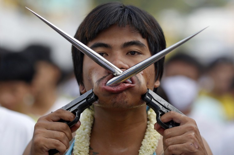 A devotee of the Chinese Bang Neow Shrine with spikes attached to plastic pistols pierced through his cheeks takes part in a procession celebrating the annual vegetarian festival in Phuket September 29, 2014. (Damir Sagolj/Reuters)