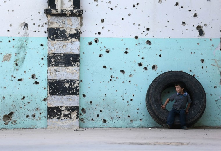 A boy sits on a wheel in front of the bullet-riddled facade of a mosque on the first day of Eid al-Adha in the Duma neighbourhood in Damascus. Muslims around the world celebrate Eid al-Adha to mark the end of the haj pilgrimage by slaughtering sheep, goats, camels and cows to commemorate Prophet Abraham's willingness to sacrifice his son, Ismail, on God's command. (Bassaf Khabieh/Reuters)