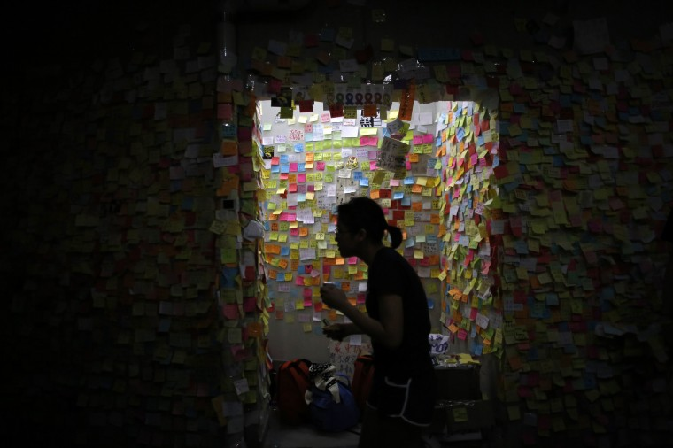 A woman looks at messages of support for the pro-democracy demonstrations on a wall, as protesters block areas around the government headquarters in Hong Kong. Hong Kong pro-democracy protest leaders said they would unblock access to government buildings to allow civil servants to go back to work next week, but defied calls from the Chinese-controlled city's leaders to end their demonstrations. (Carlos Barria/Reuters)