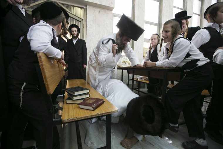 "An Ultra-Orthodox Jewish man uses a belt to hit another during ""Malkot"" or Flagellation ritual to atone for his sins for the Yom Kippur in a synagogue in the town of Beit Shemesh, near Jerusalem, ahead of Yom Kippur, the Jewish Day of Atonement, which starts at sundown Friday. (Baz Ratner/Reuters)"