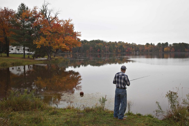 With the fall colors reflected in a lake, a man fishes for bass as it rains in Jeffersonville, New York October 11, 2014. (Carlo Allegri/Reuters)
