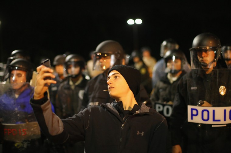 A demonstrator takes a selfie in front of a police line during a protest outside the Ferguson police department on October 10, 2014 in Ferguson, Missouri. Ferguson has been plagued with protests since the death of 18-year-old Michael Brown who was shot and killed by Darren Wilson, a Ferguson police officer on August 9. (Photo by Scott Olson/Getty Images)