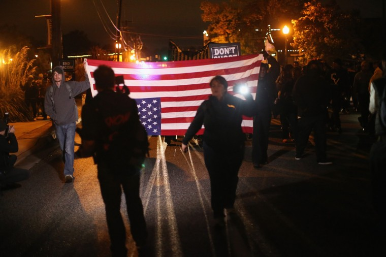 Demonstrators protest outside the Ferguson police department on October 10, 2014 in Ferguson, Missouri. Ferguson has been plagued with protests which have sometimes turned violent since the death of 18-year-old Michael Brown who was shot and killed by Darren Wilson, a Ferguson police officer, on August 9. (Photo by Scott Olson/Getty Images)