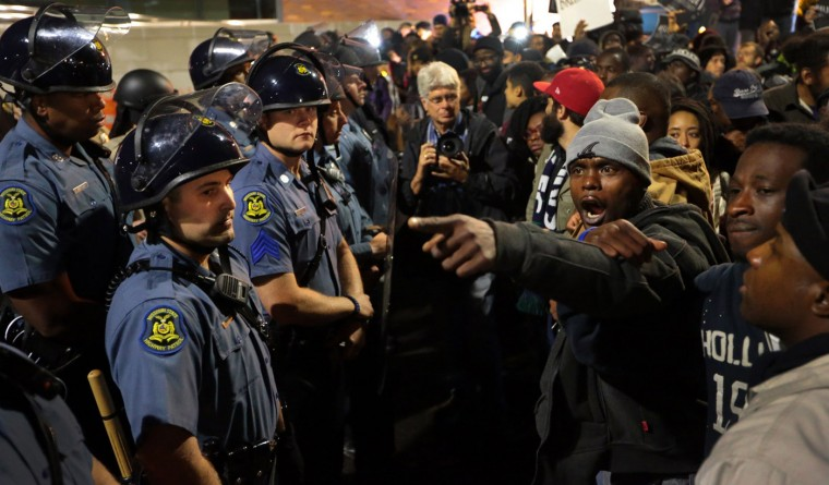 Protesters lock arms as they stand before a line of Missouri State Highway Patrol troopers in front of the Ferguson Police Department on Friday, Oct. 10, 2014. (Robert Cohen/St. Louis Post-Dispatch/MCT)