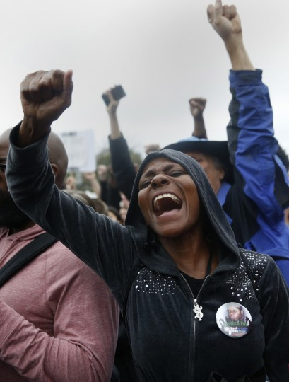 Protesters rally during a demonstration outside the Ferguson police department in Ferguson, Missouri October 13, 2014. Hundreds of civil rights activists and protesters applauded speakers, preachers and poets on Sunday in a an arena in St. Louis, Missouri, capping a weekend of protests against police violence that included 17 arrests earlier in the day. (Shannon Stapleton/Reuters)