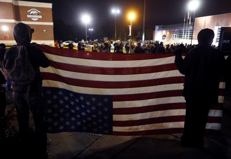 Protesters hold an American flag upside-down during a protest in Ferguson, Missouri October 10, 2014. Civil rights organizations and protest groups have invited people from around the country to join vigils and marches from Friday to Monday over the Aug. 9 shooting of Michael Brown. (Jim Young/Reuters)