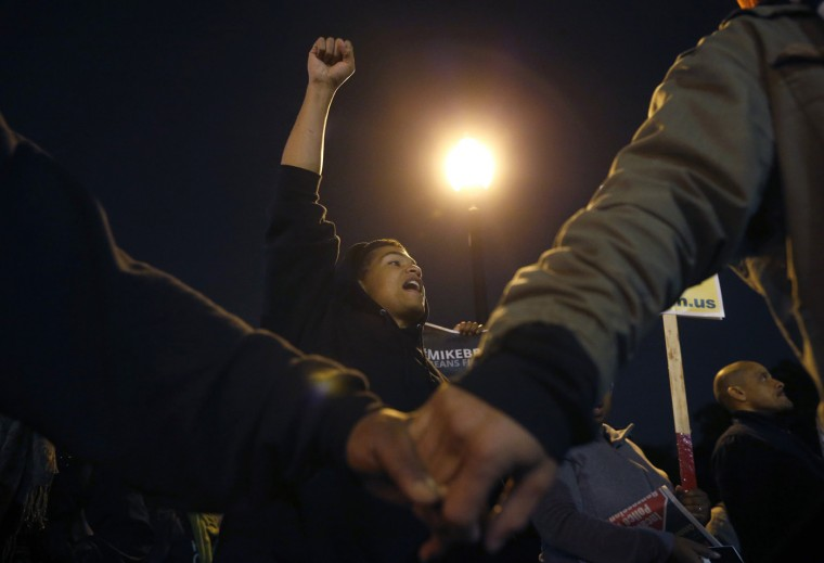 Protesters hold hands and demonstrate across the street from the police station in Ferguson, Missouri October 10, 2014. Civil rights organizations and protest groups have invited people from around the country to join vigils and marches from Friday to Monday over the Aug. 9 shooting of Michael Brown. (Jim Young/Reuters)