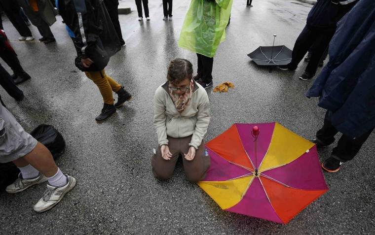 A protestor kneels down on the ground in prayer during a demonstration at the Ferguson Police Department in Ferguson, Missouri, October 13, 2014. Hundreds of protesters converged in the pouring rain on the Ferguson, Missouri, police department on Monday as they launched another day of demonstrations over the August killing by police of an unarmed black teenager. (Jim Young/Reuters)