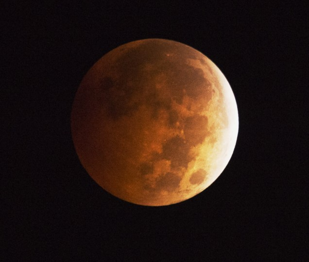The moon appears to be to have an orange-red hue as the earth's shadow covers the moon during a total lunar eclipse, in Griffith Park in Los Angeles, California October 8, 2014. A total lunar eclipse is sometimes called a blood moon because of the red color that is cast upon it by light refracting in Earth's atmosphere. (Robyn Beck/AFP/Getty Images)