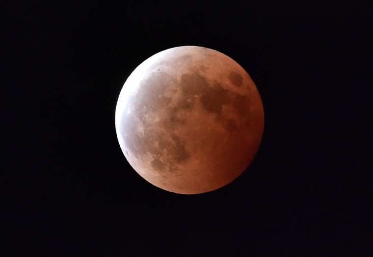 A lunar eclipse is seen in Tokyo on October 8, 2014. In Tokyo's Roppongi fashion and entertainment district, enthusiasts were planning to perform yoga exercises under the blood moon. Many others had climbed atop the city's skyscrapers to view the sky. (Yoshikazu Tsuno/AFP/Getty Images)