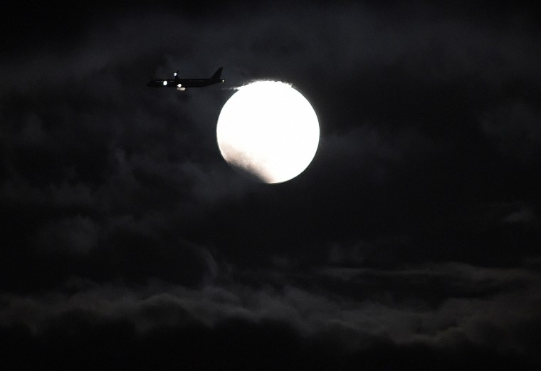 A plane flies before the moon at the beginning of a total lunar eclipse in Yokkaichi, central Japan, on October 8, 2014. In Tokyo's Roppongi fashion and entertainment district, enthusiasts were planning to perform yoga exercises under the blood moon. Many others had climbed atop the city's skyscrapers to view the sky. (Toru Yamanaka/AFP/Getty Images)