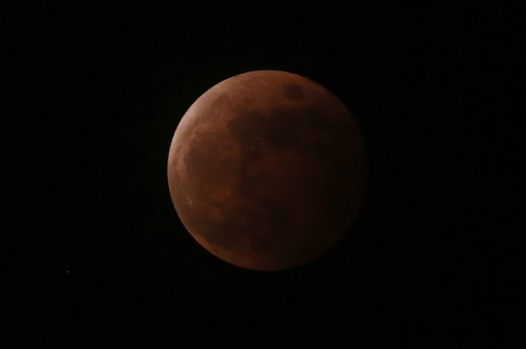 "The moon turns orange during a total lunar eclipse as seen from Taguig, Metro Manila October 8, 2014. The eclipse is also known as a ""blood moon"" due to the coppery, reddish color the moon takes as it passes into Earth's shadow. The total eclipse is the second of four over a two-year period that began April 15 and concludes on Sept. 28, 2015. The so-called tetrad is unusual because the full eclipses are visible in all or parts of the United States, according to retired NASA astrophysicist Fred Espenak. October 1, 2014. (Erik De Castro/Reuters)"