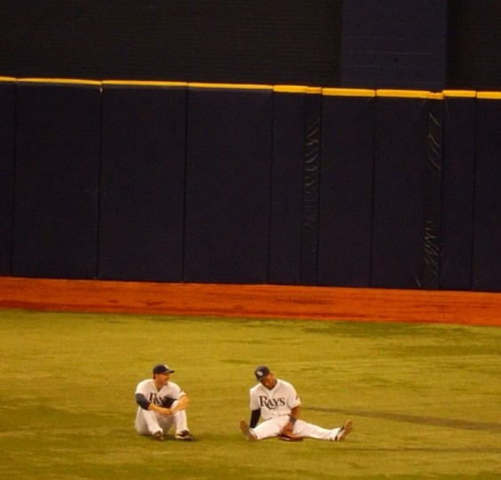 Rays outfielders Matt Joyce and Desmond Jennings sit in the Trop outfield waiting out Tuesday's 19-minute delay when a bank of lights went out on May 9, 2014.
