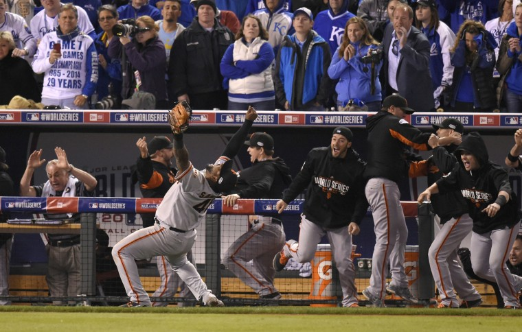 The San Francisco Giants poured out of the dugout after third baseman Pablo Sandoval, left, with arms up, catches a pop up by the Kansas City Royals' Salvador Perez to end a 3-2 Giants victory in Game 7 of the World Series on Wednesday, Oct. 29, 2014, at Kauffman Stadium in Kansas City, Mo. (Rich Sugg/Kansas City Star/MCT)