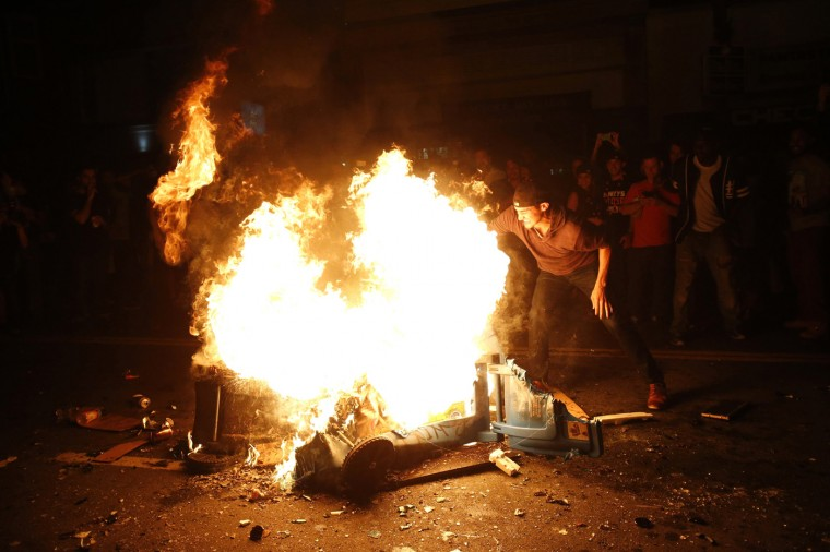 A reveller reaches into the fire that was started in celebration in San Francisco, California October 29, 2014. The San Francisco Giants beat the Kansas City Royals 3-2 on Wednesday to win their third World Series title in five seasons. (Stephen Lam/Reuters)