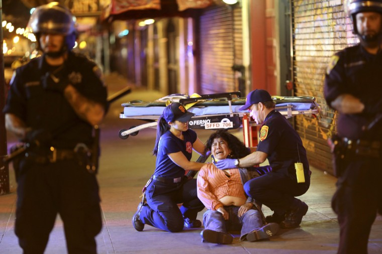 A woman is assisted by medical personnel during a celebration in the Mission District in San Francisco, California October 29, 2014. The San Francisco Giants beat the Kansas City Royals 3-2 on Wednesday to win their third World Series title in five seasons. (Robert Galbraith/Reuters)