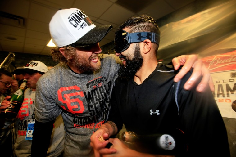 Hunter Pence #8 and Sergio Romo #54 of the San Francisco Giants celebrate in the locker room following a 3-2 victory over the Kansas City Royals in Game Seven of the 2014 World Series at Kauffman Stadium on October 29, 2014 in Kansas City, Missouri. (Photo by Jamie Squire/Getty Images)