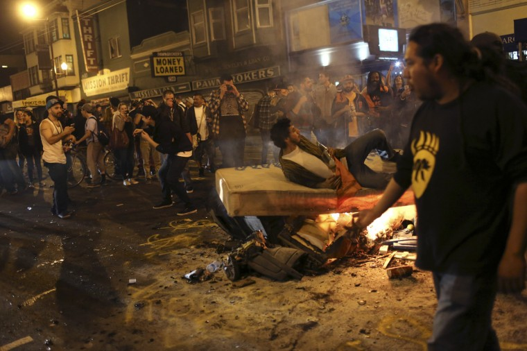 A man lays on a burning mattress set ablaze along the street in the Mission District during a celebration after the San Francisco Giants defeated the Kansas City Royals in Game 7 of the World Series, in San Francisco, California October 29, 2014. (Robert Galbraith/Reuters)