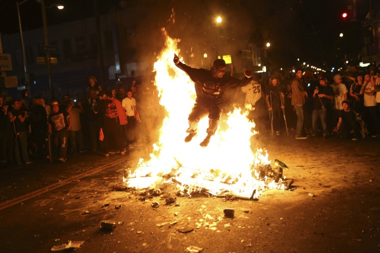 A man jumps through a fire along a street in the Mission District during a celebration after the San Francisco Giants defeated the Kansas City Royals in Game 7 of the World Series, in San Francisco, California October 29, 2014. (Robert Galbraith/Reuters)