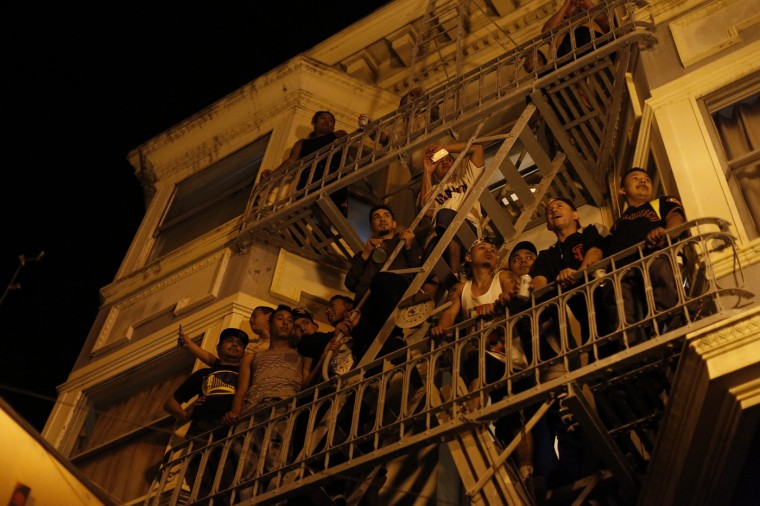 People watch a street celebration from a balcony in San Francisco, California October 29, 2014. The San Francisco Giants beat the Kansas City Royals 3-2 on Wednesday to win their third World Series title in five seasons. (Stephen Lam/Reuters)