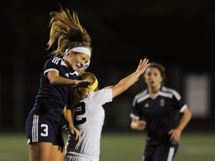 Perry Hall's Taylor Francis, left, collides with Catonsville's Jenn Nonn, center, while going for a header during a sectional final soccer game at Catonsville High School on Thursday, Oct. 30, 2014. (Jon Sham/BSMG)