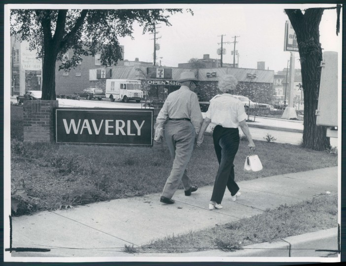 7/17/79: An elderly couple walks hand in hand beneath the trees of East 33rd street and East University parkway in Waverly. (Ralph L. Robinson)