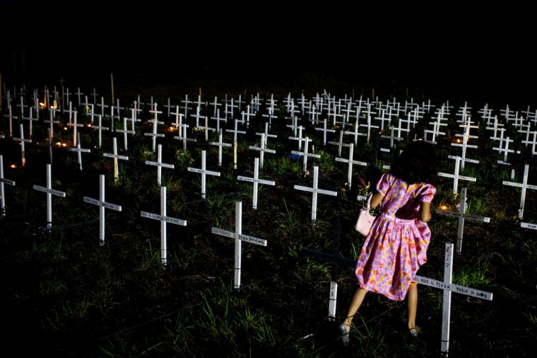 A young girl walks between crosses as she tries to find the grave of a loved one at a newly constructed mass grave for 3,000 typhoon Haiyan victims on the grounds of the Holy Cross Cemetery during All Souls Day in Tacloban, Leyte, Philippines. Filipinos descend on cemetaries all across the country to tend to the graves of loved ones on November 1-2 marking All Saints day and All Souls day. Residents of Leyte are preparing for the 1-year anniversary since Super Typhoon Yolanda struck the coast on November 8, 2013, leaving more than 6000 dead and many more homeless. (Chris McGrath/Getty Images)