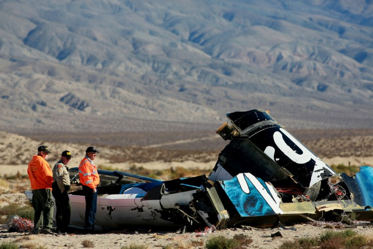 Sheriff's deputies inspect the wreckage of the Virgin Galactic SpaceShip 2 in a desert field north of Mojave, California on The Virgin Galactic SpaceShip 2 crashed on October 31, 2014 during a test flight, killing one pilot and seriously injuring another. (Sandy Huffaker/Getty Images)