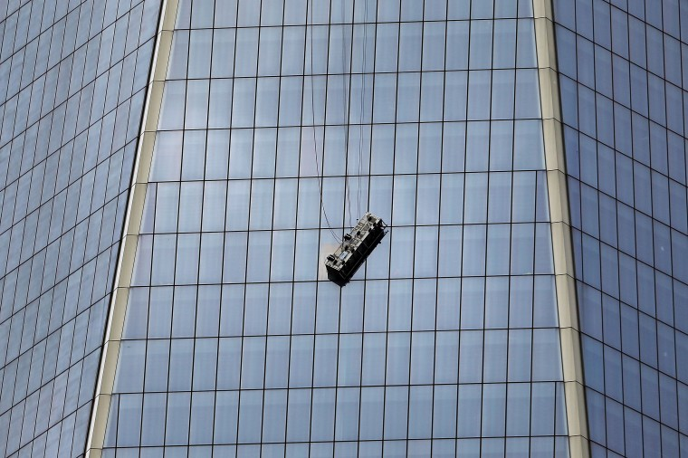 A scaffold carrying two workers hangs 69 floors up at One World Trade Center on November 12, 2014 in New York City. The workers were washing windows 69 floors up soon after 1 World Trade Center, the tallest building in the Western Hemisphere, opened. (Photo by Spencer Platt/Getty Images)