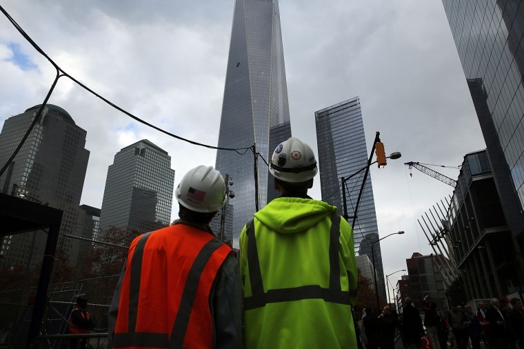 Construction workers look up at scaffold carrying two workers hanging 69 floors up at One World Trade Center on November 12, 2014 in New York City. The workers were washing windows 69 floors up soon after 1 World Trade Center, the tallest building in the Western Hemisphere, opened. (Photo by Spencer Platt/Getty Images)