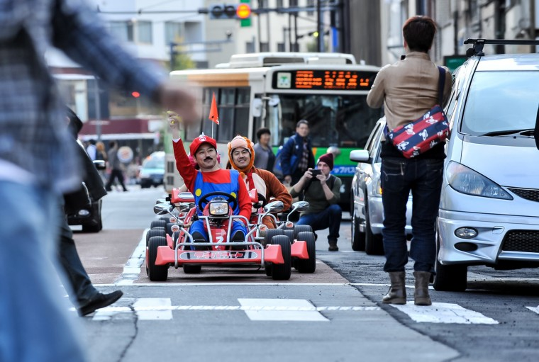 People take photos of participants as they drive around Tokyo in Mario Kart characters for the Real Mario Kart event in Tokyo in Tokyo, Japan. The organizer calls for participants to this event held about once a month on Facebook, and Akiba Kart offers rental karts that can be driven on public streets. (Keith Tsuji/Getty Images)