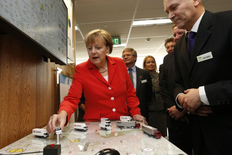 Germany's Chancellor Angela Merkel plays with models of trucks during an interactive demonstration of transportation logistics during her visit to the Future Logistics Living Lab on November 17, 2014 in Sydney, Australia. German Chancellor Angela Merkel is attending meetings in Sydney following the G20 Leaders Summit in Brisbane. (Jason Reed/Getty Images)