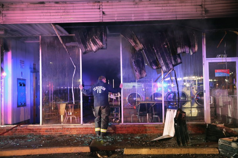 A Ferguson firefighter surveys damage at a strip mall that was set on fire when rioting erupted following the grand jury announcement in the Michael Brown case on November 25, 2014 in Ferguson, Missouri. Brown, an 18-year-old black man, was killed by Darren Wilson, a white Ferguson police officer, on August 9. At least 12 buildings were torched and more than 50 people were arrested during the night-long rioting. (Photo by Scott Olson/Getty Images)
