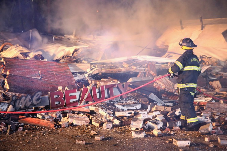 A Ferguson firefighter surveys rubble at a strip mall that was set on fire when rioting erupted following the grand jury announcement in the Michael Brown case on November 25, 2014 in Ferguson, Missouri. Brown, an 18-year-old black man, was killed by Darren Wilson, a white Ferguson police officer, on August 9. At least 12 buildings were torched and more than 50 people were arrested during the night-long rioting. (Photo by Scott Olson/Getty Images)