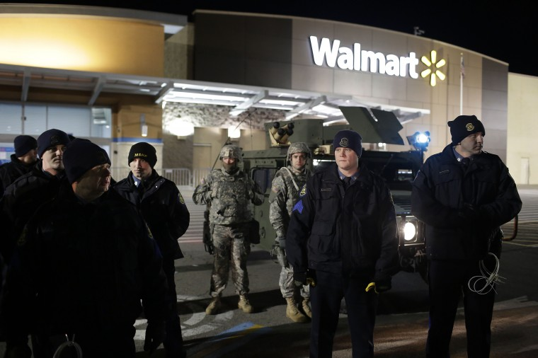 Police officers and National Guard troops stand outside of a closed Walmart November 27, 2014 in Ferguson, Missouri. Local businesses still remain closed to consumers in Ferguson as tension continue to still run high the community after Michael Brown, a 18-year-old black male teenager was fatally wounded by Darren Wilson, a white Ferguson Police officer on August 9, 2014. A St. Louis County 12-member grand jury who reviewed evidence related to the shooting decided Monday not to indict Wilson with charges sparking riots through out Ferguson. (Photo by Joshua Lott/Getty Images)