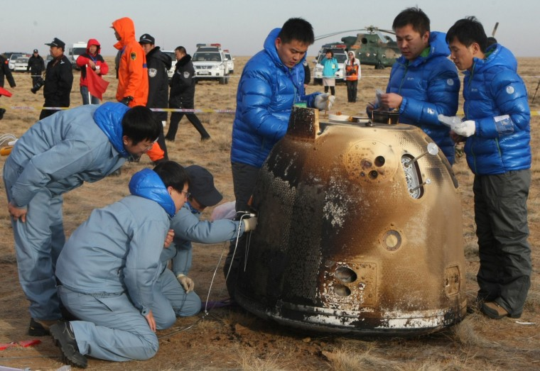 Technicians check the unmanned probe landed in Dorbod (Siziwang) Banner, north China's Inner Mongolia region. China completed its first return mission to the moon early with the successful re-entry and landing of an unmanned probe, state media reported, in the latest step forward for Beijing's ambitious space program. (Getty Images)