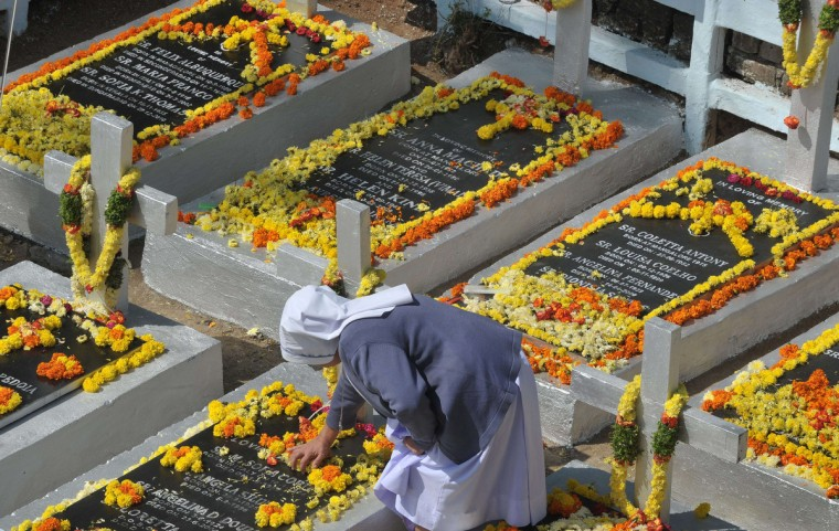 An Indian Catholic nun decorates the graves of deceased sisters at a Catholic Cemetery during All Souls Day in Hyderabad. All Souls Day is a Roman Catholic day observed in remembrance of friends and loved ones who have passed away. The living pray on behalf of Christians who are in purgatory, the state in the after life where souls are purified before proceeding to heaven. (Noah Seelam/Getty Images)