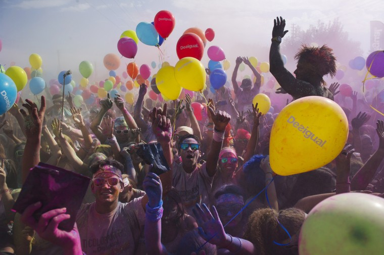 Runners dance after taking part in the Color Run of Sevilla. The Color Run is a race where participants are showered with colored powder after each kilometer. (Cristina Quicler/Getty Images)