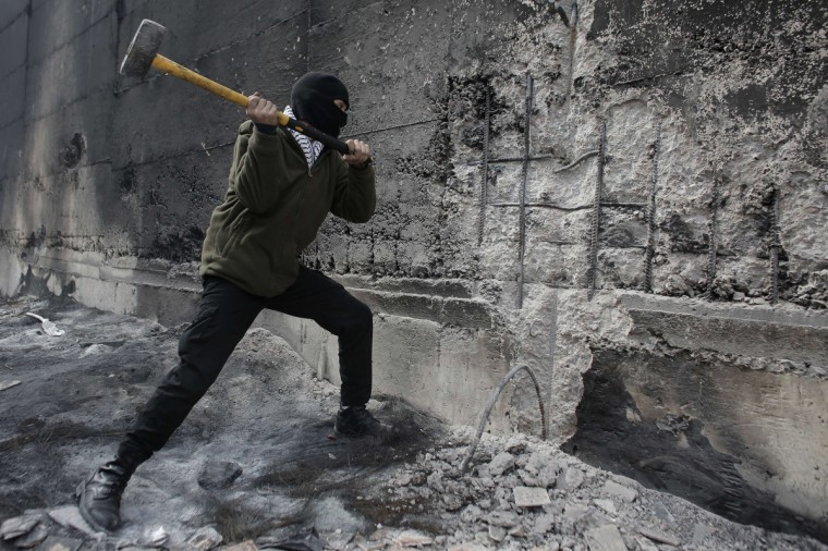 A Palestinian protester tries to hammer a hole through Israel's controversial barrier that separates the West Bank town of Abu Dis from Jerusalem. A Palestinian bus driver, whose family lives in Abu Dis, was found hanged in his vehicle in west Jerusalem overnight, in what Israeli police said was an apparent suicide but a colleague said looked like murder. (Ahmad Gharabli/Getty Images)