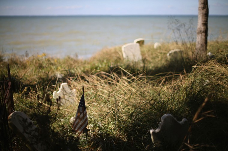 Graves sit at the waters edge of the Anchor of Hope Cemetery which is slowly eroding away from the rising waters of the Chesapeake Bay. October 8, 2014 in Hoopers Island, Maryland. Donny Willey has volunteered his time to try and save the cemetery from erosion but cannot get a permit from the state of Maryland to erect a seawall. The cemetery is the resting place of more than 150 men, women, and children. Individuals from the War of 1812 to slaves and freed slaves, from the founding family of Hoopers Island to veterans of several wars are buried here. Several islands in the Chesapeake Bay region are slowly eroding away as sea levels are projected to rise several feet over the next century. (Photo by Mark Wilson/Getty Images)