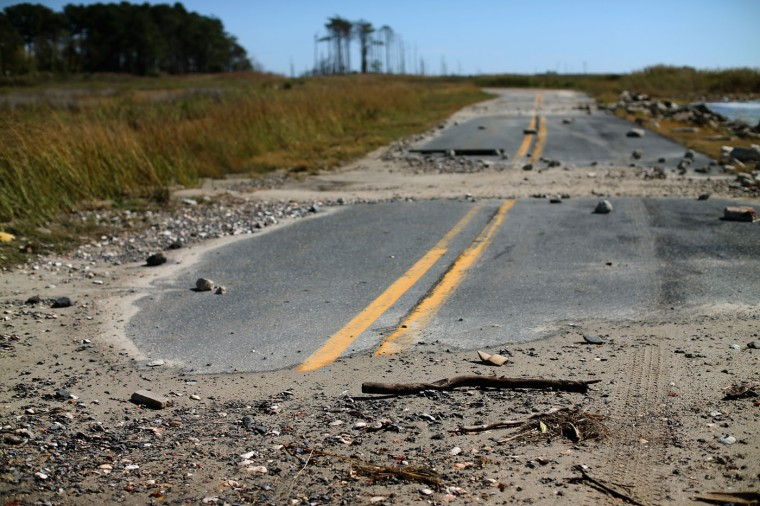 Sand and debris cover a road after a Chesapeake Bay high tide earlier in the week October 8, 2014 in Hoopers Island, Maryland. Several islands in the Chesapeake Bay region are slowly eroding away as sea levels are projected to rise several feet over the next century. (Photo by Mark Wilson/Getty Images)