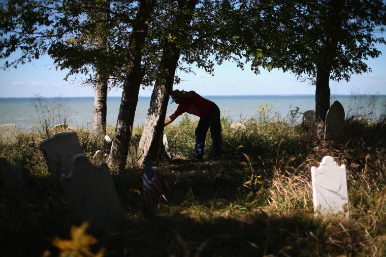 Donny Willey straightens grave markers at the Anchor of Hope Cemetery that is slowly eroding into the Chesapeake Bay. October 8, 2014 in Hoopers Island, Maryland. Willey has volunteered his time to try and save the cemetery from erosion but cannot get a permit from the state of Maryland to erect a seawall. The cemetery is the resting place of more than 150 men, women, and children. Individuals from the War of 1812 to slaves and freed slaves, from the founding family of Hoopers Island to veterans of several wars are buried here. Several islands in the Chesapeake Bay region are slowly eroding away as sea levels are projected to rise several feet over the next century. (Photo by Mark Wilson/Getty Images)