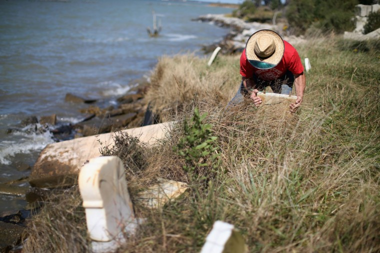 Donny Willey moves back grave markers at the Anchor of Hope Cemetery that is slowly eroding into the Chesapeake Bay. October 8, 2014 in Hoopers Island, Maryland. Willey has volunteered his time to try and save the cemetery from erosion but cannot get a permit from the state of Maryland to erect a seawall. The cemetery is the resting place of more than 150 men, women, and children. Individuals from the War of 1812 to slaves and freed slaves, from the founding family of Hoopers Island to veterans of several wars are buried here. Several islands in the Chesapeake Bay region are slowly eroding away as sea levels are projected to rise several feet over the next century. (Photo by Mark Wilson/Getty Images)