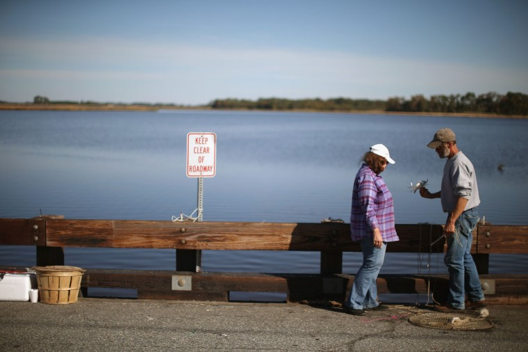 Mike Huber shows his wife Janet look at a crab he just caught while crabbing on a bridge October 9, 2014 in Church Creek, Maryland. Several islands and property located at sea level in the lower Chesapeake Bay region are slowly eroding away as sea levels rise. Officials have projected the sea level will rise several feet over the next century leaving many of the Chesapeake bay's lower islands underwater. (Photo by Mark Wilson/Getty Images)